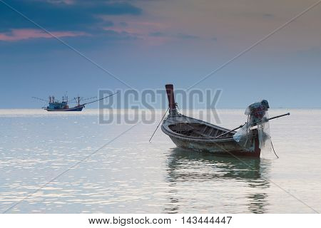Long tail boat sitting in seacoast skyline, natural landscape background