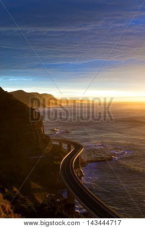 Aerial view of Sea Cliff bridge at sunrise dusk with sunbeams and sunrays. Australian roads and infrastructure. Sightseeing tourist destination in Stanwell Tops park NSW Australia