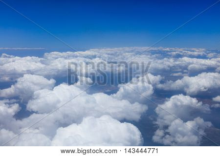 Aerial view of blue sky above white clouds floating under land