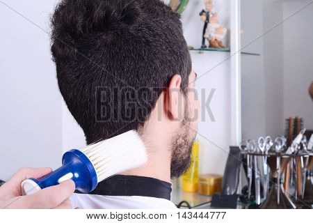 Close up of a young man in a hairdressing salon at the end of a haircut. Indoors.