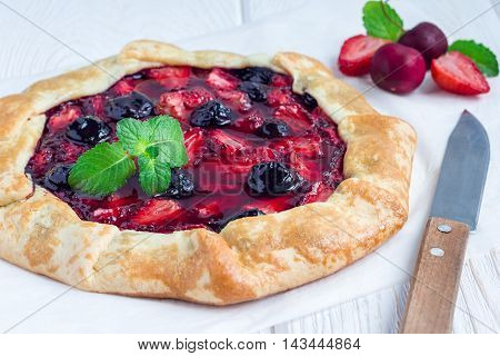 Cottage cheese dough galette with strawberry and cherry on wooden table horizontal