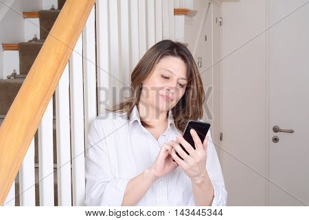Portrait of beautiful businesswoman at home and sending messages. Indoors.