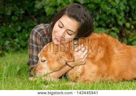 A female shares a moment with her dog in the backyard