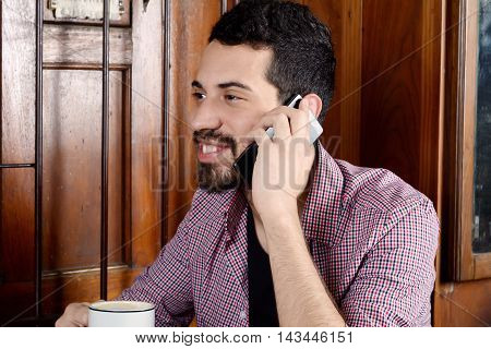 Portrait of young latin man talking on phone and drinking coffee in a cafe. Indoors.