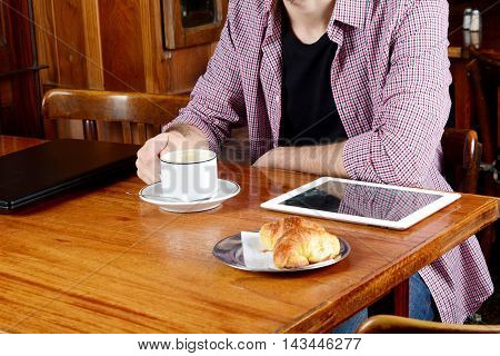Close up of young man drinking coffee with laptop and digital tablet at a cafe. Indoors.