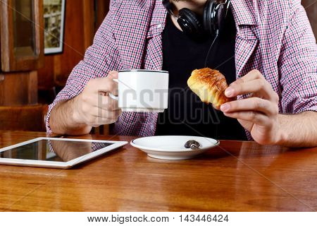 Portrait of young latin man drinking coffee and eating with headphones and digital tablet at a cafe. Indoors.