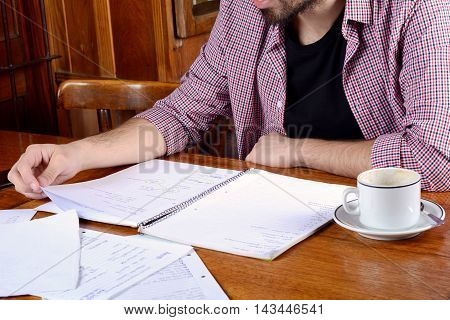 Portrait of young latin student reading his notes and a cup of coffee at a cafe. Indoors.