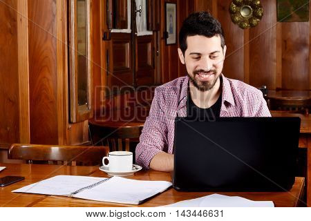 Portrait of young latin student using laptop with cup of coffee at a cafe. Indoors.