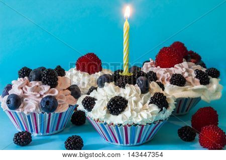 CUPCAKES WITH CREAM AND BERRIES, WITH A LIGHTED CANDLE ON BLUE BACKGROUND