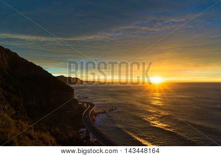 Sea cliff bridge along Australian Pacific ocean coast on sunrise. Sun rising out of sea with sun rays and sun flare visible. NSW Australia
