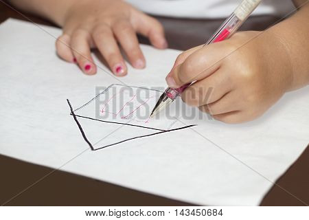 Little girl's hands with ballpen drawing a house on a white paper