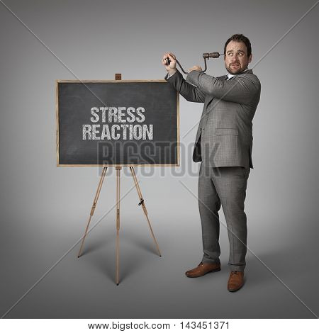 Stress reaction text on blackboard with businessman drilling his head