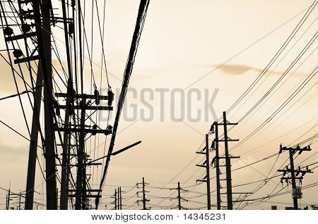 Silhouettes of telegraph poles and cables with copy space