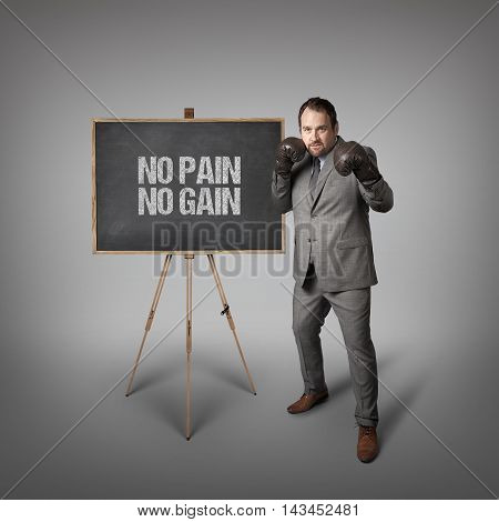 No pain no gain text on  blackboard with businessman wearing boxing gloves