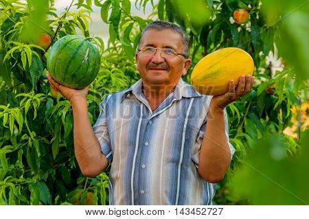 An old man is holding a water-melon in his right hand and a melon in his left hand. He is smiling. He is happy to have a good harvest, He is standing in the background of a peach tree. You can see peaches in it