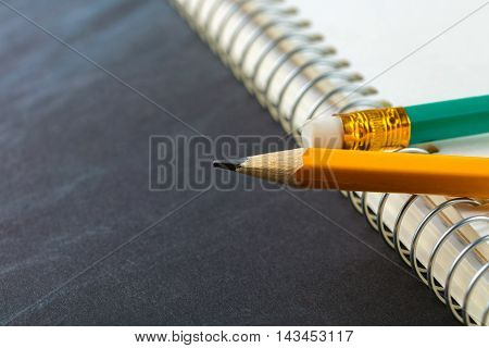 sharpened pencil and a notebook on black background