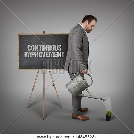 Continuous improvement text on  blackboard with businessman watering plant