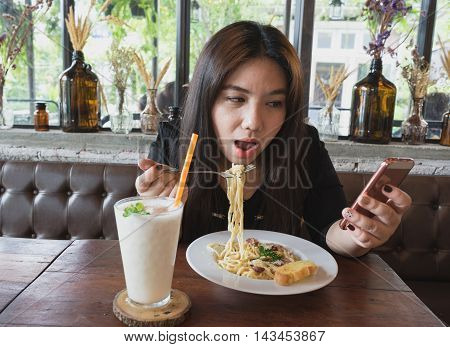 woman look at mobile phone social network take selfie photo picture with lychee juice and carbonara spaghetti at restaurant with wooden table and relax atmosphere