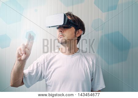 Man with VR goggles working in virtual reality environment casual male person exploring modern technology.