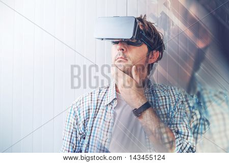 Man with VR goggles exploring virtual reality content and enjoying in cyberspace environment digital glitch effects added in post production.