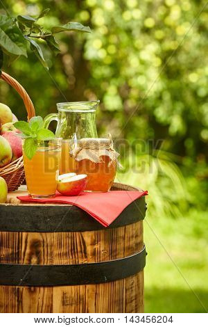 Basket of apples on background orchard standing on a barrel. Apple juice and apple preserves.