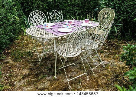 Garden iron table prepared for breakfast in a relaxing corner