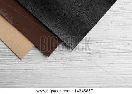 Pieces of quality leather on wooden table