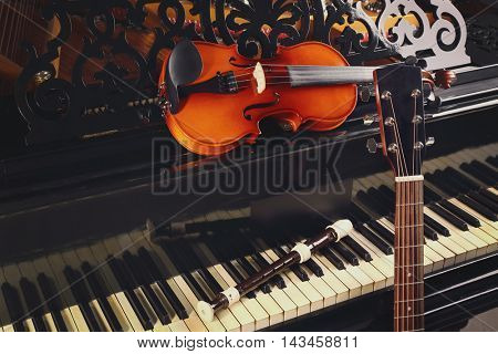 Flute, violin and guitar neck on piano