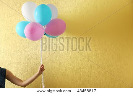 Colourful toy air balloons on yellow background