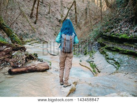 Traveler young woman with backpack walking along mountain river rear view
