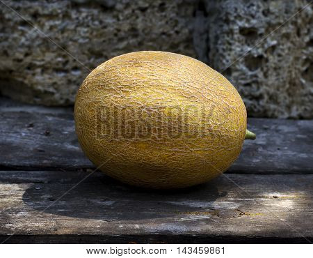 Ripe melon on a wooden table and a stone background