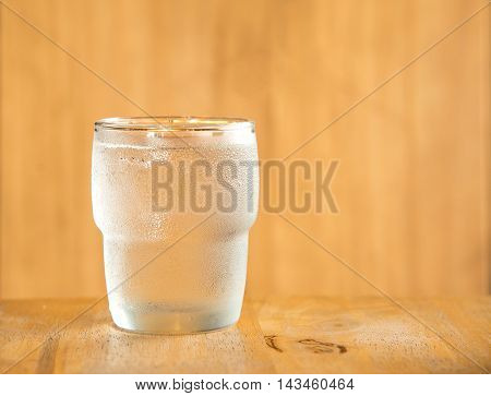 Glass off water on a wooden table.