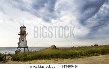 Old lighthouse with a cloudy sky by the Black sea