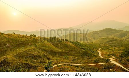 Defocus of mountain landscape and valley road with orange sky at sunset Thailand. Background of hill landscape. Nature and environment concept.
