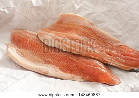 Close up of two fresh pink trout fillets from the fishmongers