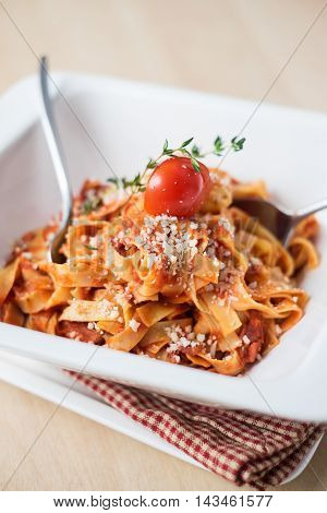 Traditional italian pasta tagliatelle with bolognese sauce or ragu with cherry tomato, thyme and parmesan cheese in a plate, selective focus