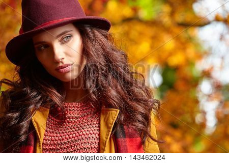 Sensual beautiful young woman in autumn park in a maroon hat