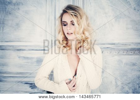 Fashion Woman with Blonde Curly Hair. Femininity and Temptation