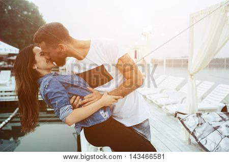 man kissing his woman on the pier at the lake