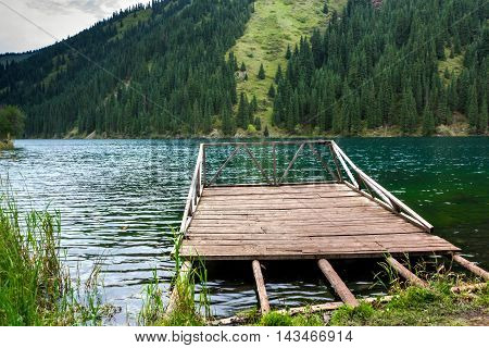 abandoned wooden pier on the shore of a mountain lake