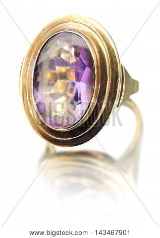 Precious gold ring with purple gemstone. Isolated on white background.