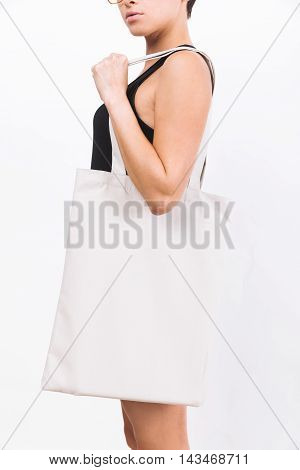 Woman in glasses with short hair is wearing black tank top and holding large cotton textile bag. Concept of product promotion and advertising. Mock up. White background.