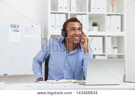 Black man listening to music and smiling while sitting at his workplace. Concept of good pastime
