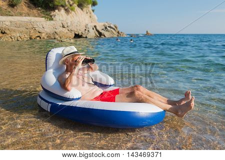 Senior man with spy glasses floating on chair in the sea