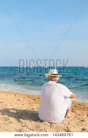 Senior man in white suit looking at the sea