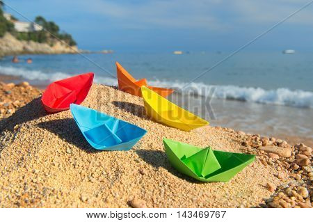 many colorful paper boats at the beach to play with