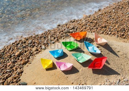 Many paper boats in the sand at the beach