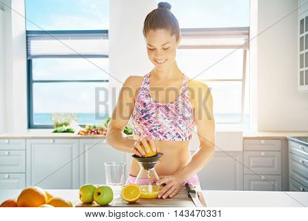 Shapely fit young woman preparing fresh fruit juice in her kitchen with a happy smile from an assortment of organic fruit copy space on a high key background