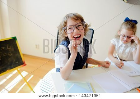 Funny little schoolchildren in glasses boy and girl sit at one desk. It's elementary school students. Children laugh. The deskmate in children are school supplies and textbooks. Back to school.