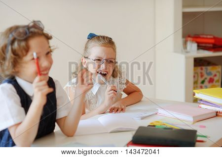 Funny little pupils sit at one desk. They are pupils of an elementary school. Boy and girl laugh. On a school desk children have school accessories and textbooks. Back to school.